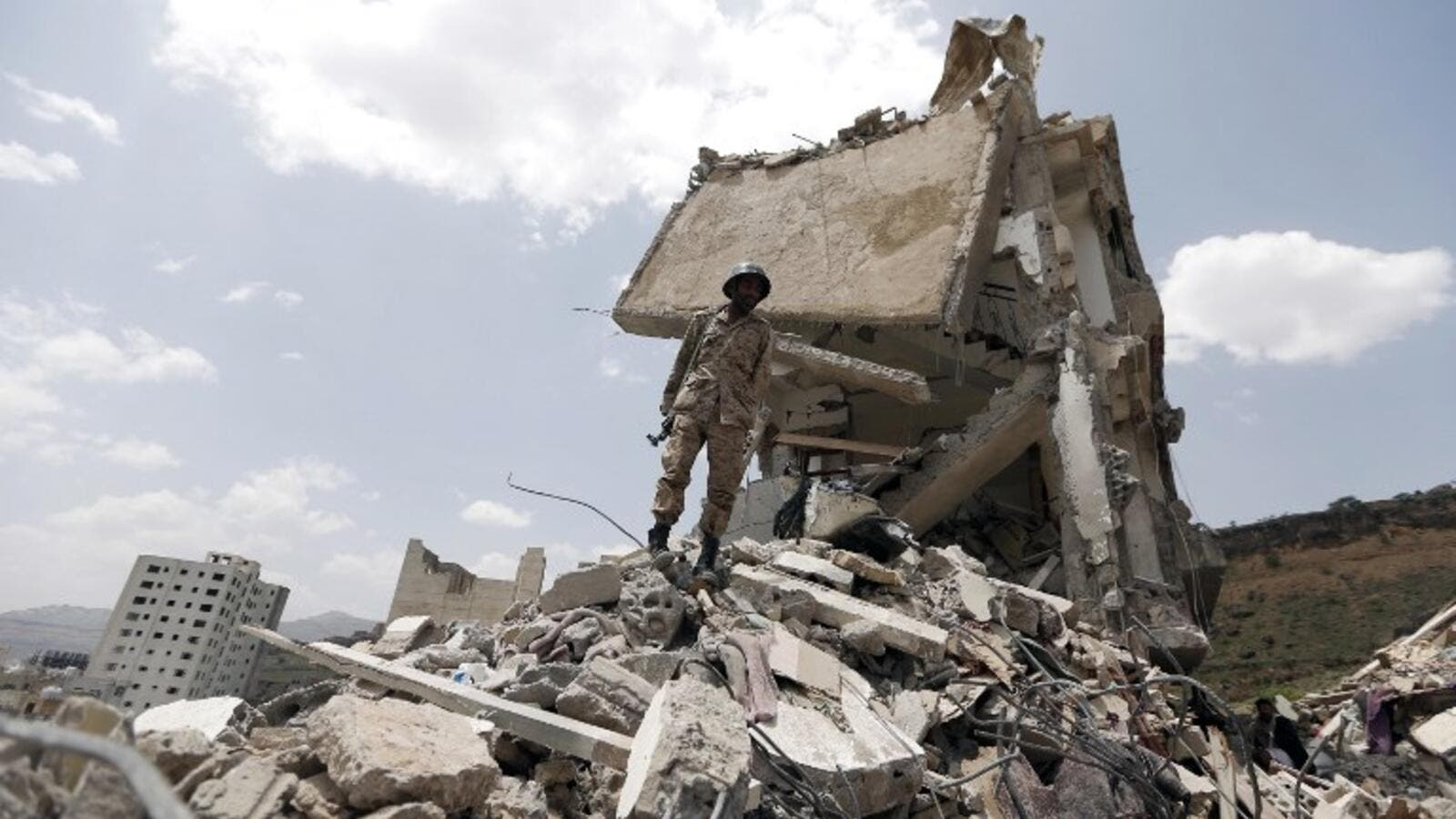 A Yemeni soldier stands on the debris of a house, hit in an air strike on a residential district, in the capital Sanaa on August 26, 2017 (AFP)