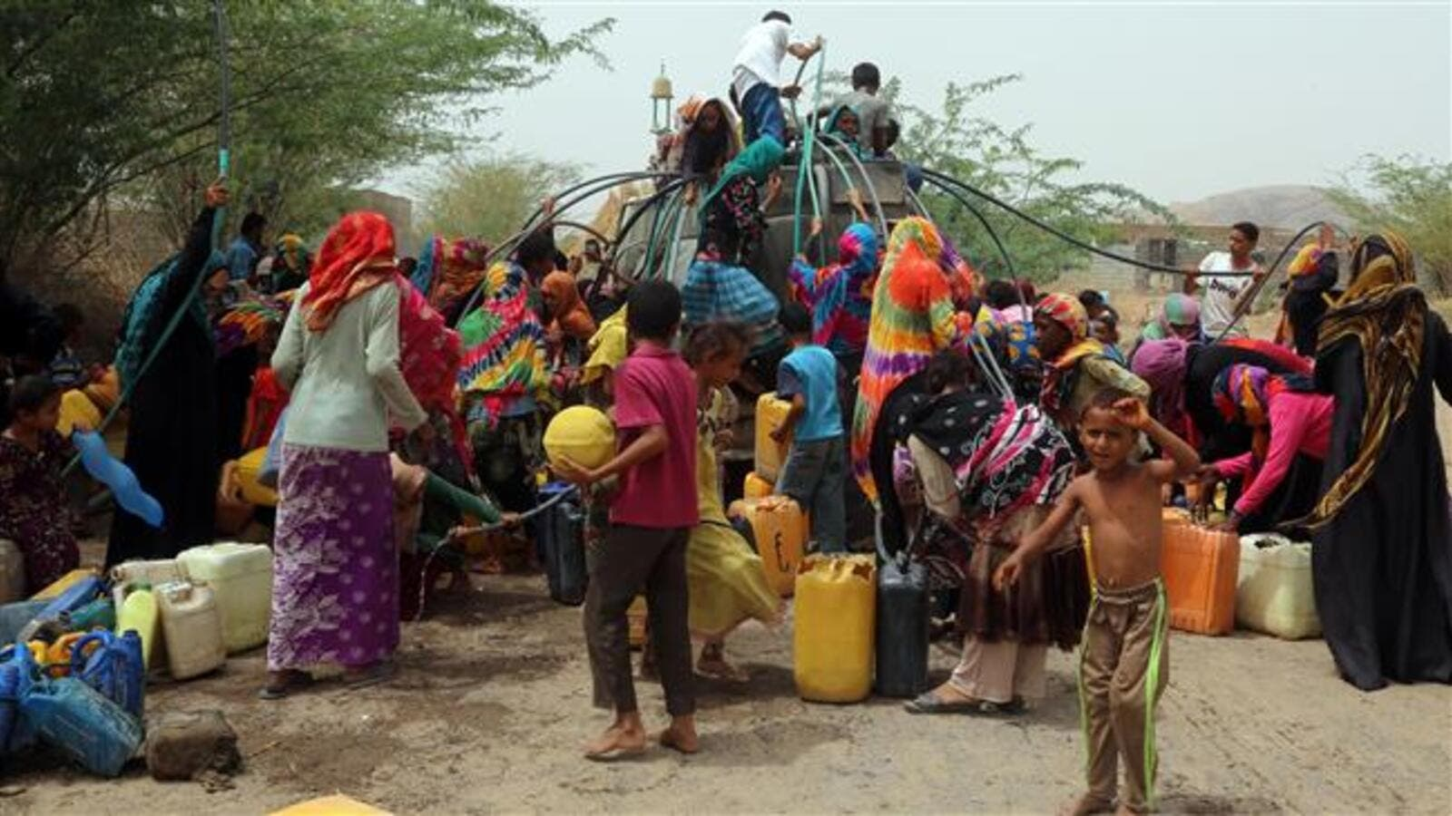 Yemenis gather next to a water tank to collect water in an impoverished coastal village on the outskirts of the Yemeni port city of Hudaydah, on May 12, 2018. (AFP Photo)