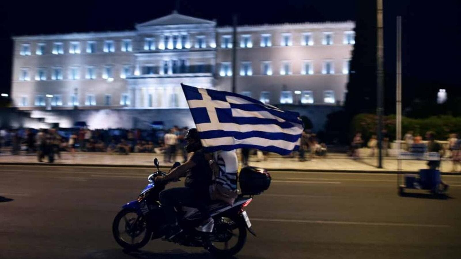 A motorcylist with his passenger holding a Greek flag passes in front of the Greek Parliament (AFP/File Photo)