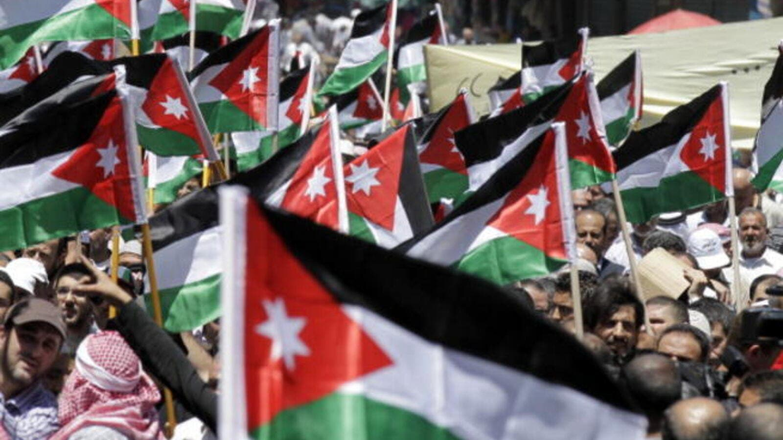 Protesters from the Islamic Action Front and other opposition parties hold up Jordanian national flags and shout slogans demanding political and economic reform, and access to cases of corruption, during a demonstration in Amman on June 14, 2013. [AFP]