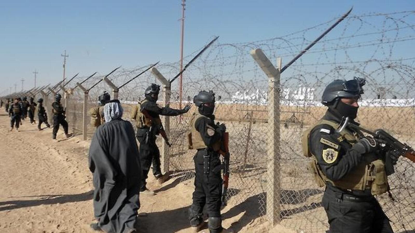 Iraqi SWAT forces stand guard outside Camp Ashraf, home to exiled Iranian opposition members. [AFP]
