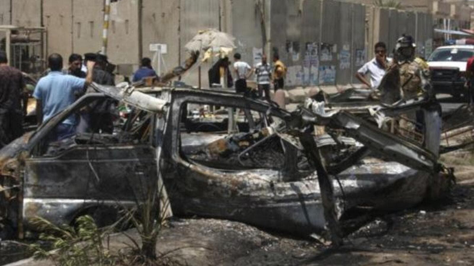 People inspect site of a car bomb attack in Iraq. [presstv]