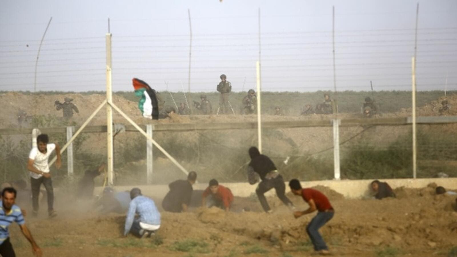 Israeli forces fire at Palestinians trying to cut border fence between Israel and Gaza Strip on Friday (AFP)