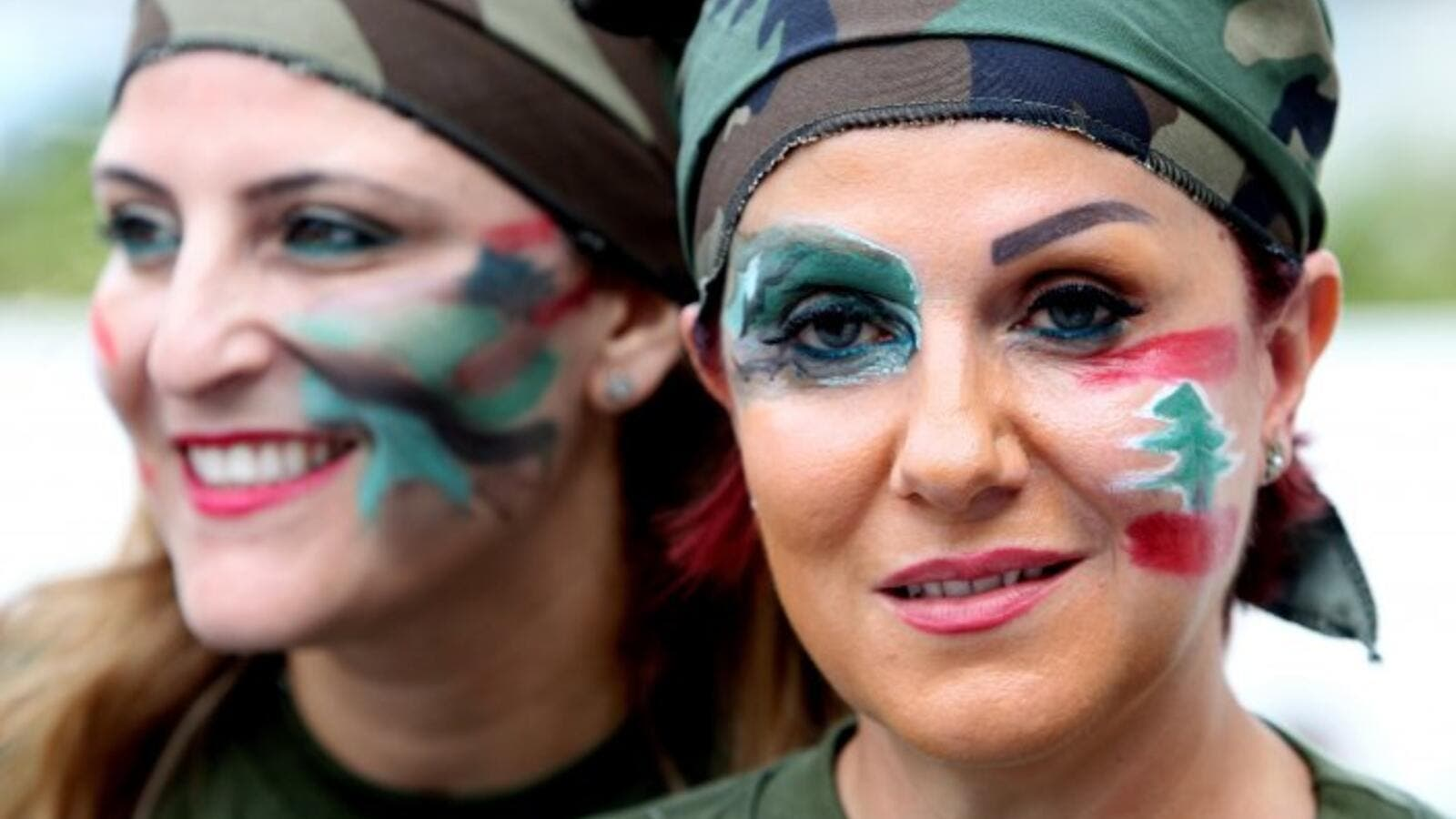Lebanese women dressed in military fatigue and their faces painted with the colors of their national flag hold a sit in at Martyrs square in downtown Beirut, in support of the Lebanese army, on August 18, 2014. (AFP/Anwar Amro)
