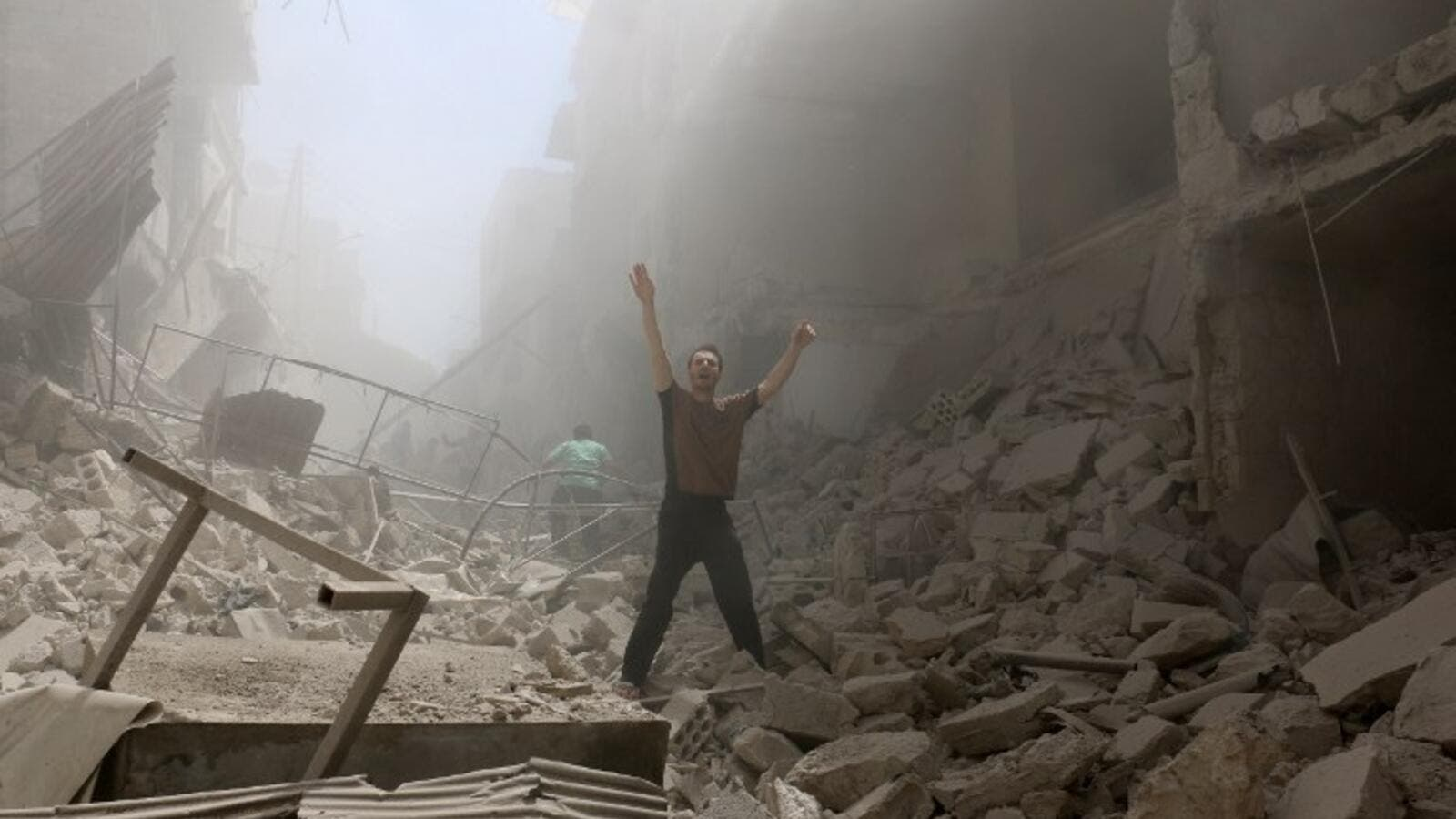 A man gestures while walking through rubble after multiple airstrikes in Aleppo today. (AFP/Amee Alhalbi)