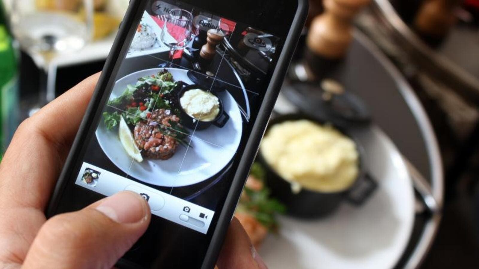 A man photographs his meal with a cell phone. Photograph by Ana Arevalo. AFP