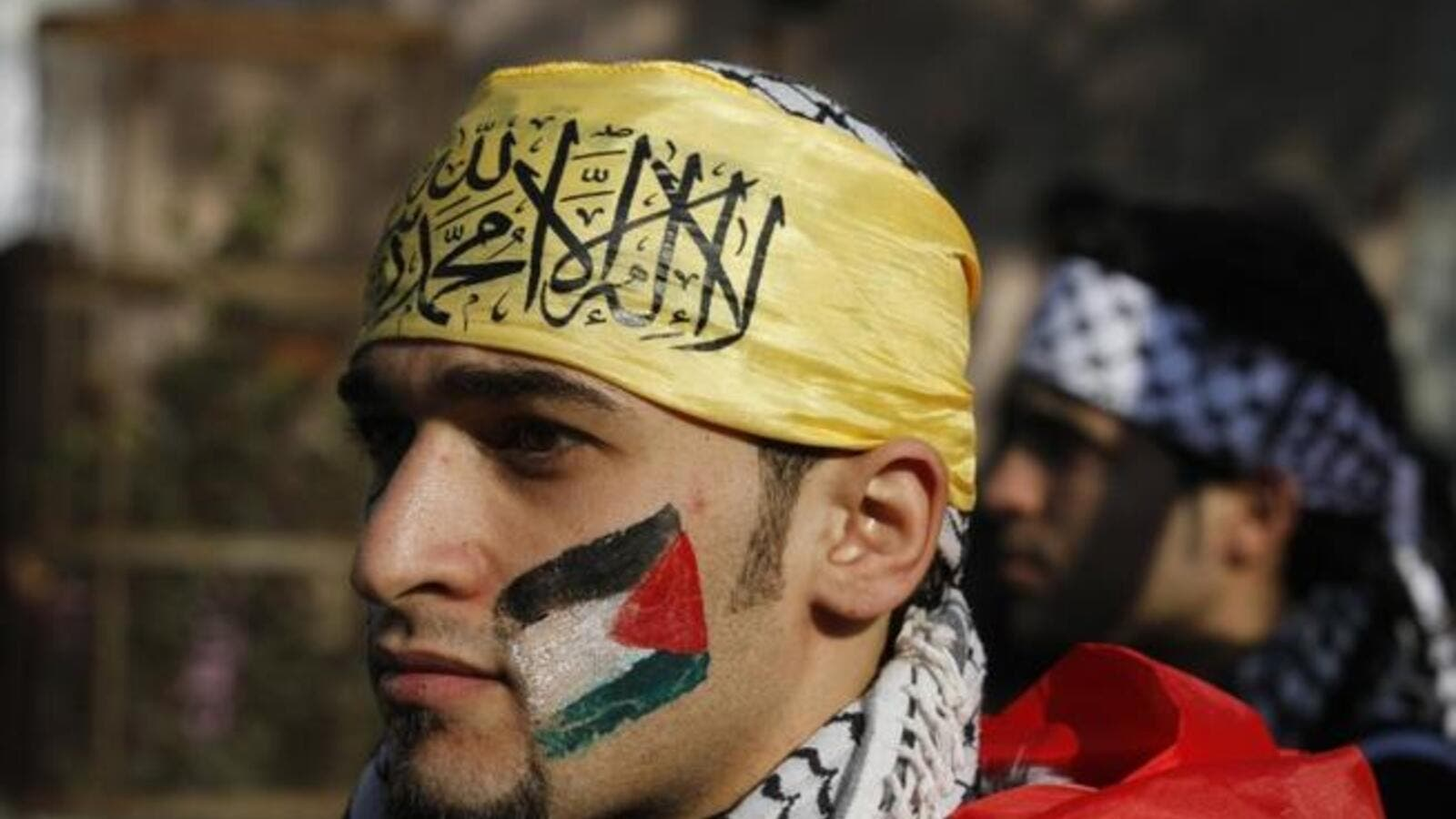 A Palestian wearing the trademark chequerred keffieyh with a national flag painted on his face, attends a rally in support of president Mahmoud Abbas's Farah party on Friday in Gaza City. (AFP PHOTO / MOHAMMED ABED)