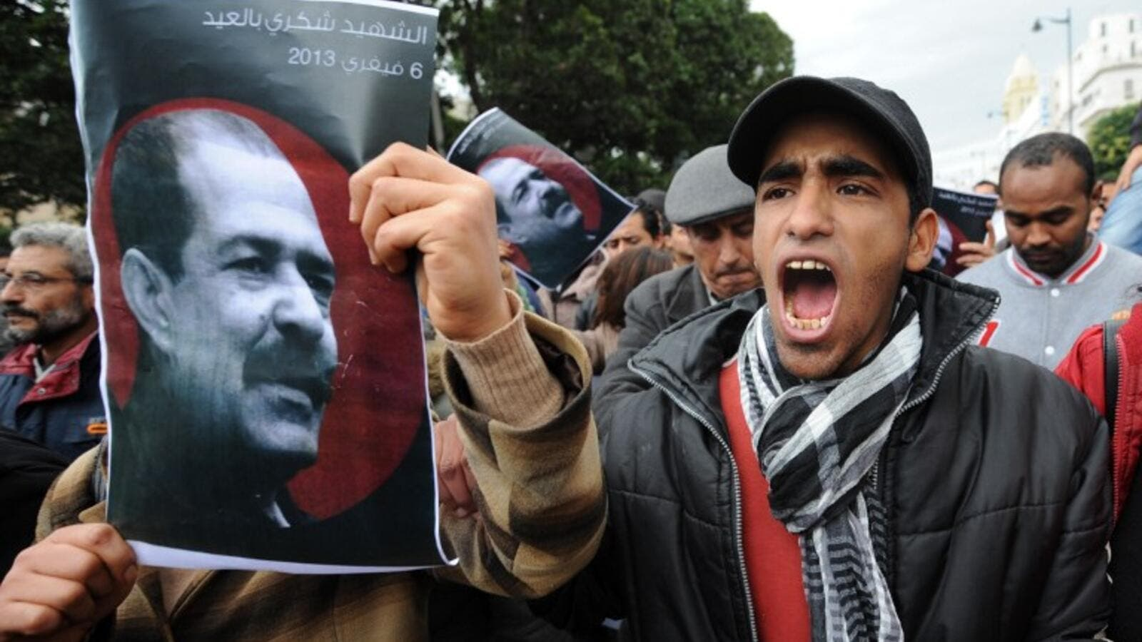 A Tunisian protestor holds a placard featuring killed opposition leader Chokri Belaid during a demonstration. (AFP PHOTO / FETHI BELAID)