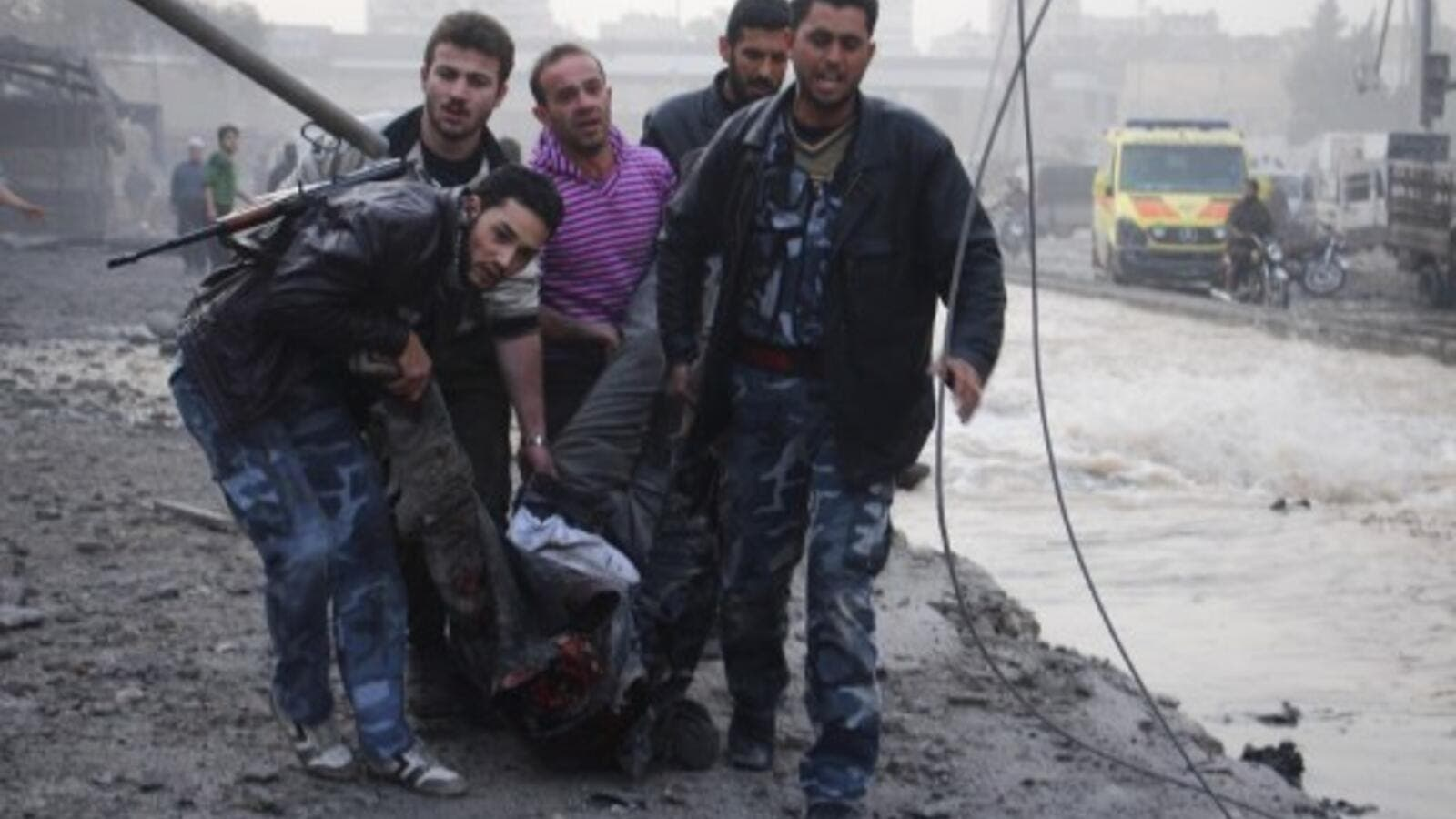Rebels and civilians carry the body of a man killed after an air strike by pro-government forces on the Syrian city of Aleppo on November 28, 2013. (AFP)