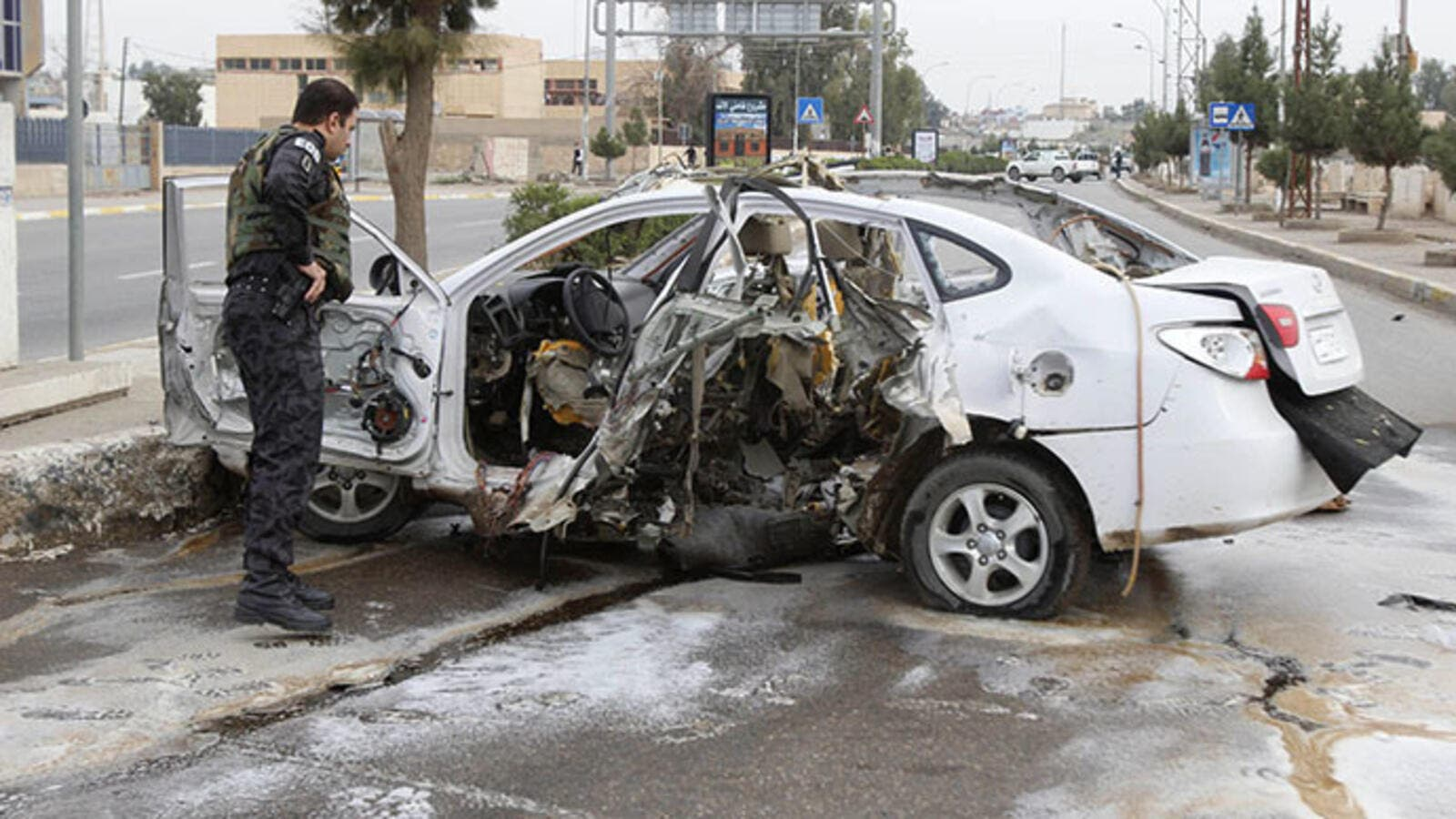 Security officials examine a car after a bomb in Kirkuk Wednesday (Reuters)