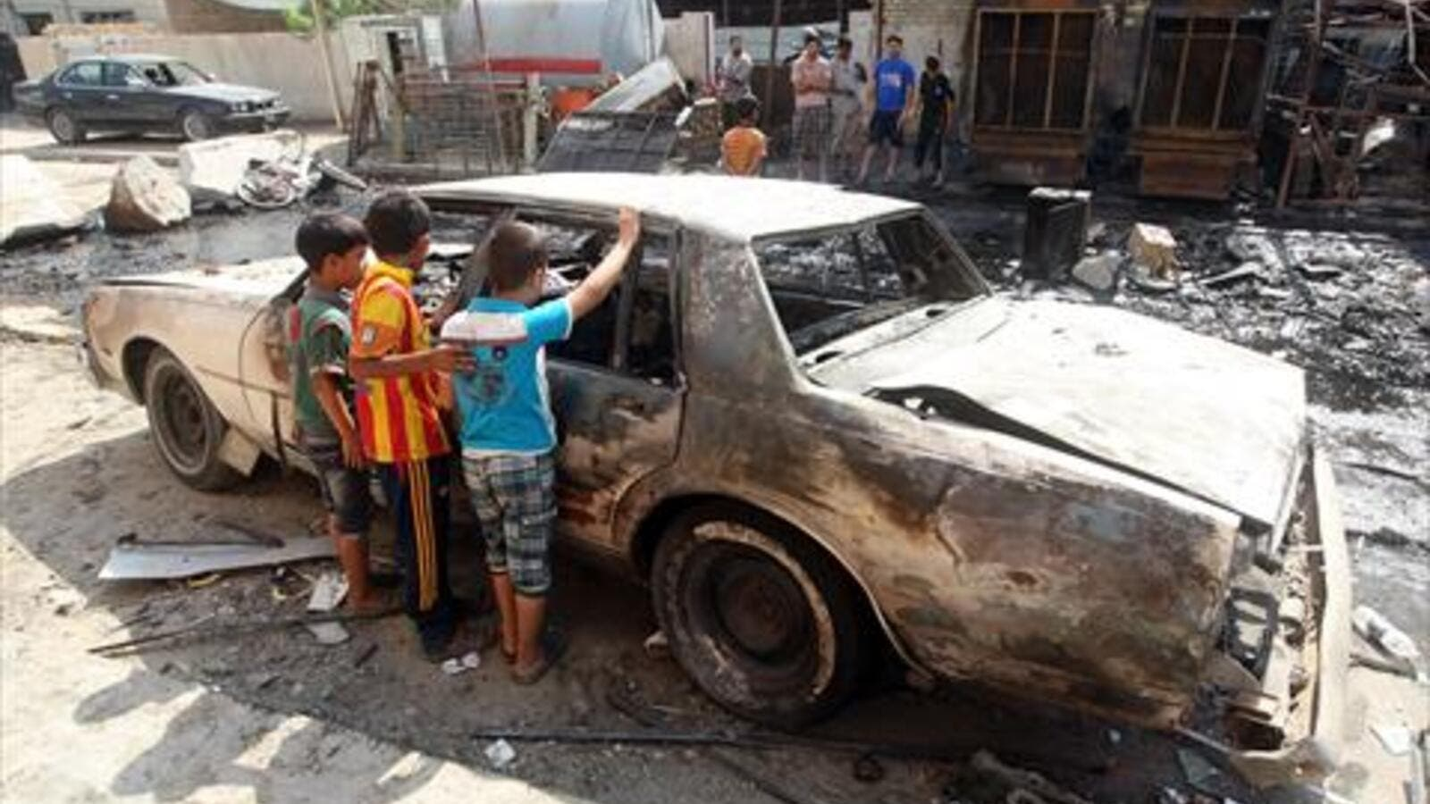 Iraqi children inspect a burnt-out car at the site of a car bomb attack that exploded the previous day in a commercial street of Baghdad's eastern neighbourhood of Mashtal on Monday. On Tuesday, a fresh wave of violence across the country killed at least 24 people. (AFP)