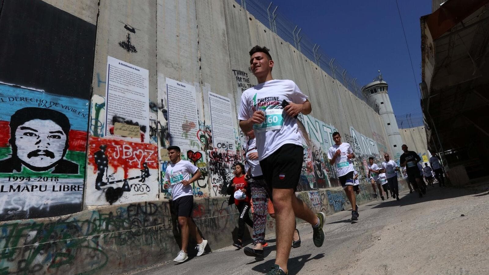 Participants in the Palestine Marathon running along the Israeli apartheid wall surrounding the biblical city of Bethlehem. (Photo: WAFA Images / Ahmad Mizher)