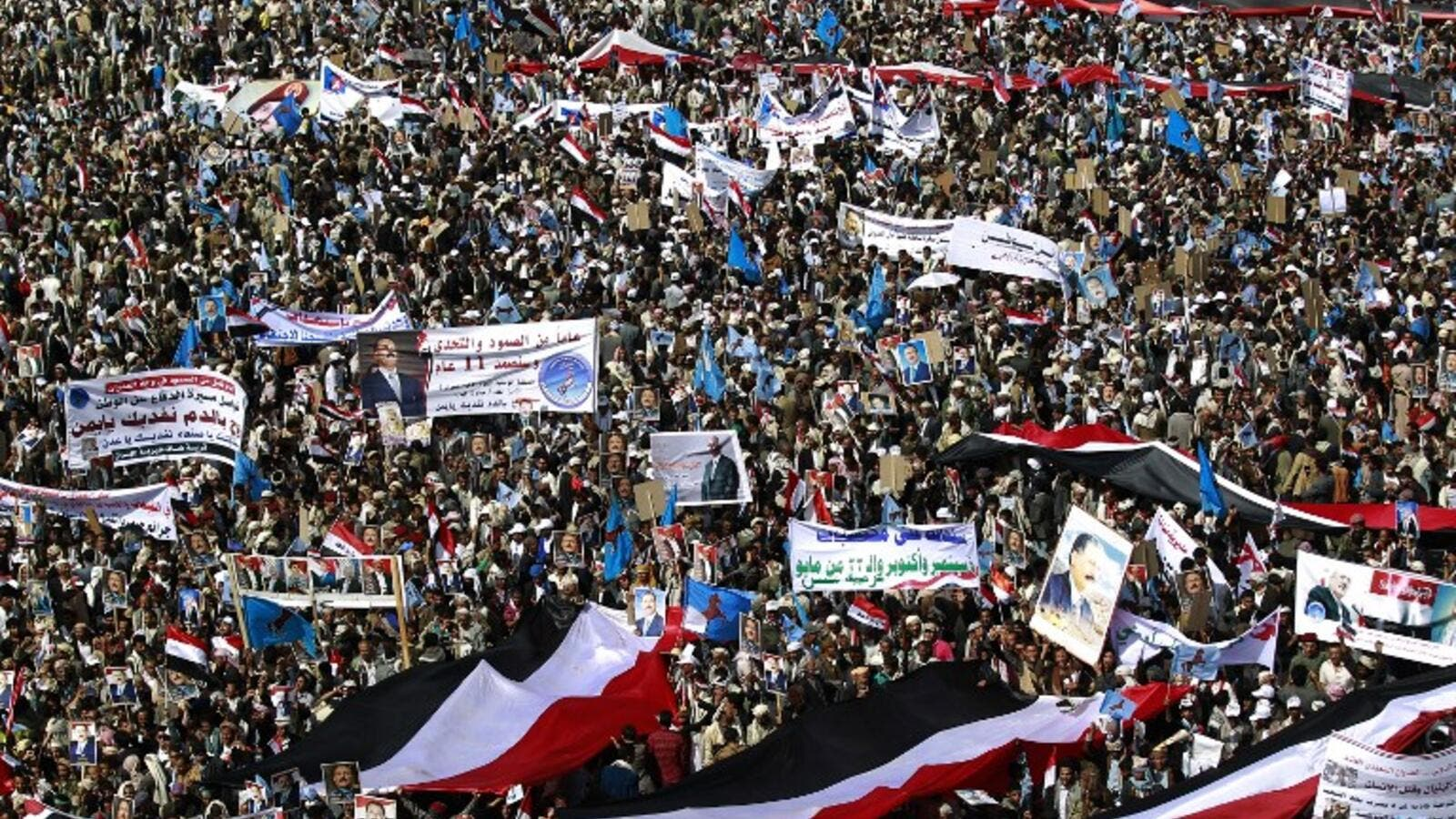 Yemenis wave national flags and hold placards during a protest against the Saudi-led coalition, commemorating one year of the alliance's military campaign against insurgents on March 26, 2016 next to the Monument to the Unknown Soldier in the Yemeni capital Sanaa. (AFP/Mohammed Huwais)