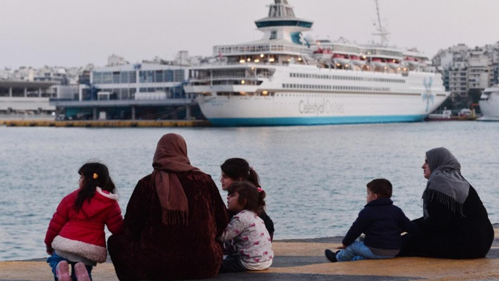 Refugee families sit on February 26, 2016 at a pier in the port of Piraeus, where hundreds of migrants and refugees, many from Syria stay temporarily. (AFP/Louisa Gouliamaki)
