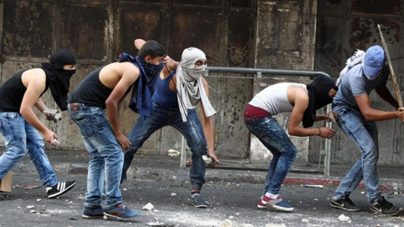 Palestinian youths throw stones towards Israeli security forces during clashes in the West Bank town of Hebron on October 4, 2015. (AFP/File)
