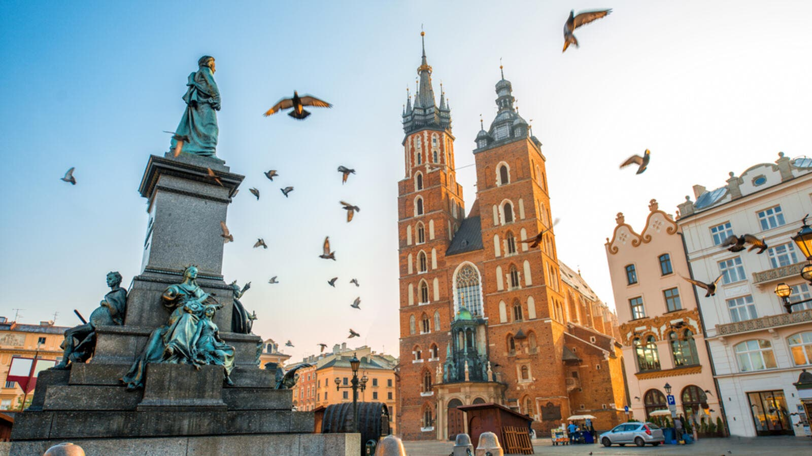 Old city center view with Adam Mickiewicz monument, St. Mary's Basilica and birds flying in Krakow (Shutterstock)