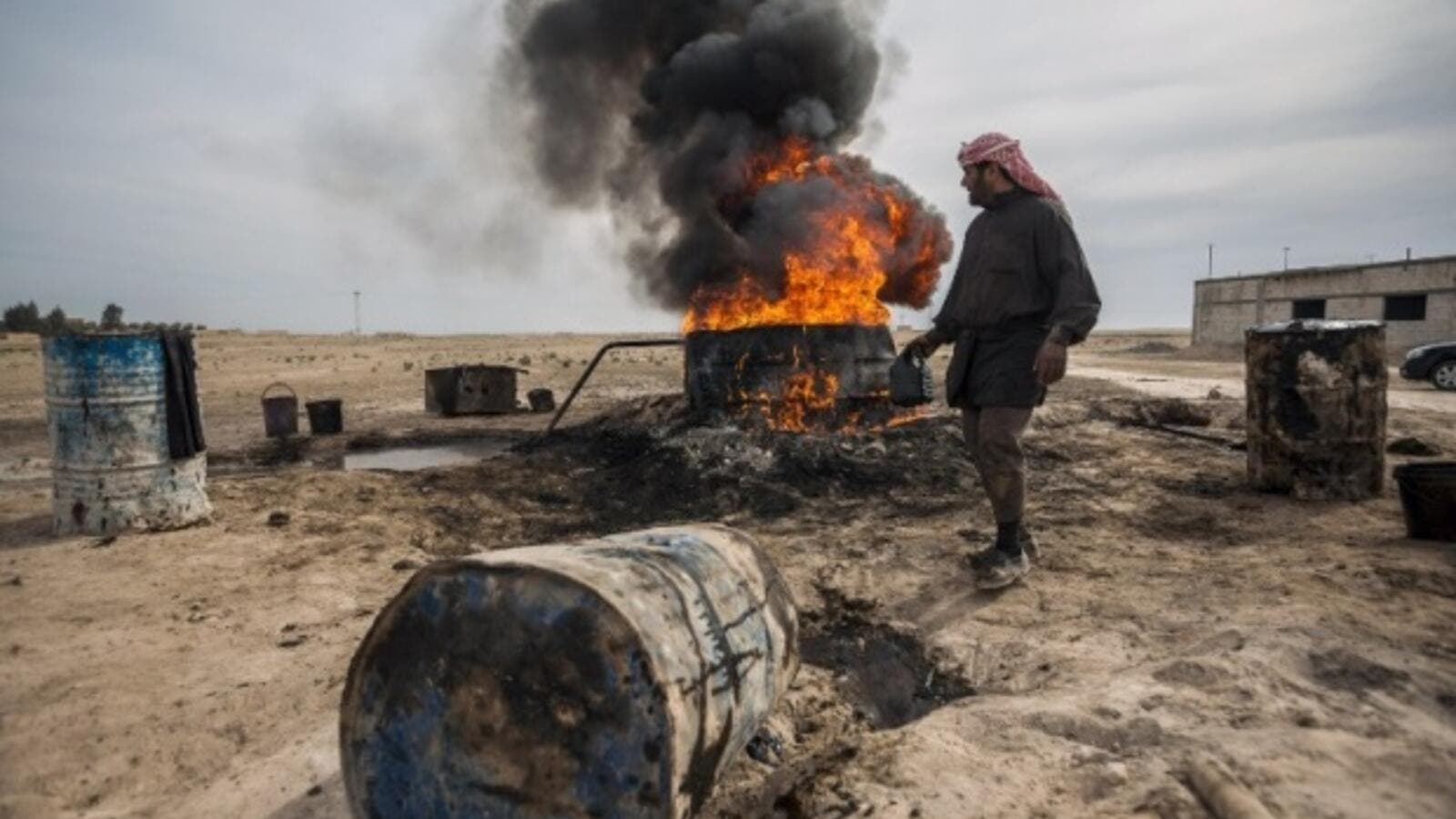 (A man processes oil through a makeshift rig in Deir Ezzour Governorate, AFP)