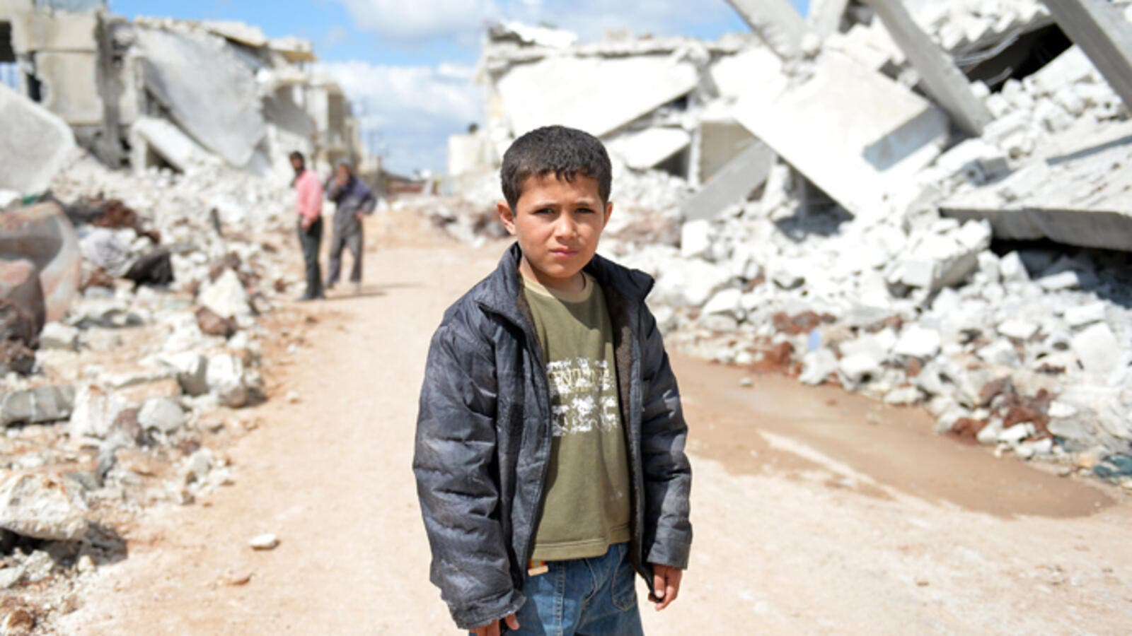 A young Syrian boy poses for a picture between destroyed houses in the northern Syrian town. (AFP/File)