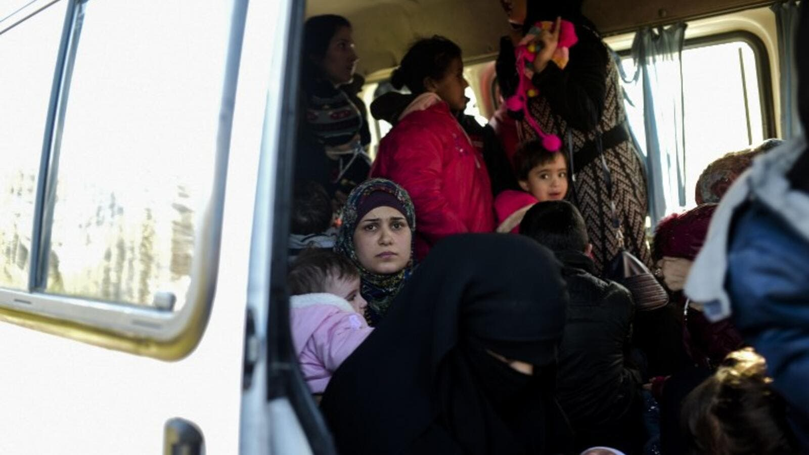 A woman looks on from inside a van after being detained by Turkish soldiers with other Syrians trying to reach the Greek island of Lesbos from Dikili, western Turkey, on March 5, 2016. (AFP/Bulent Kilic)