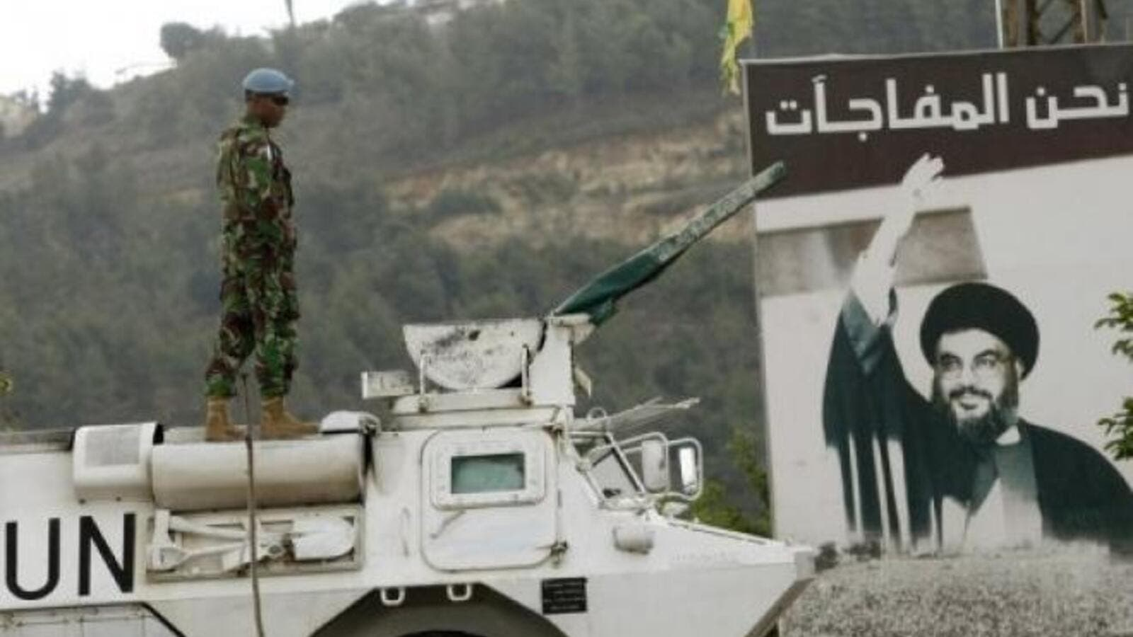 A UN peacekeeper is seen near Lebanon's Blue Line, with a picture of the Hezbollah leader Hassan Nasrallah in the background. (AFP/File)