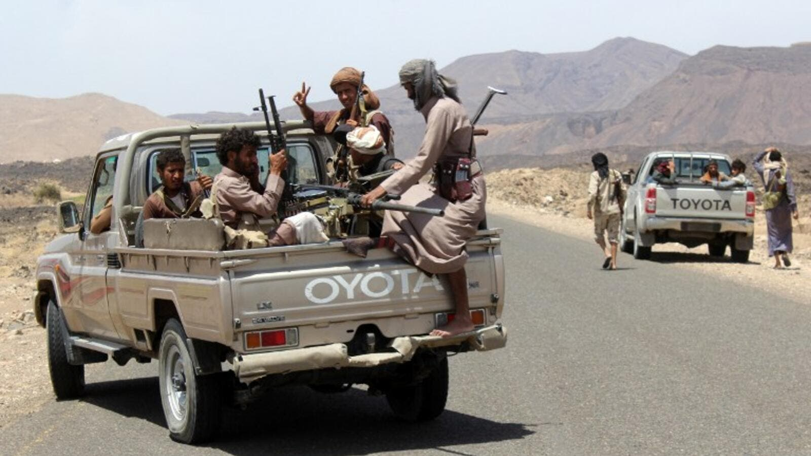 Yemeni fighters loyal to exiled President Abed Rabbo Mansour Hadi wait in their pick-up trucks on a road in the Sirwah area, in Marib province on April 9, 2016. (AFP/Nabil Hassan)