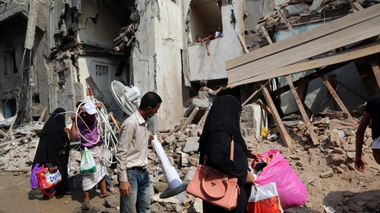 Yemenis carry belongings they recovered from the rubble of buildings destroyed during Saudi-led air strikes the previous day, on September 22, 2016 in the rebel-held Yemeni port city of Hodeida. (AFP/Stringer)