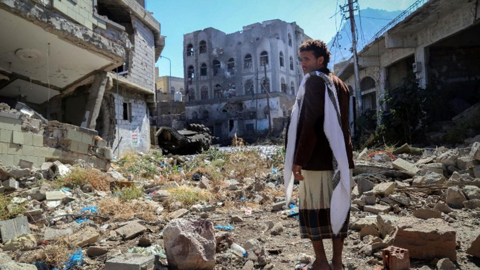 A Yemeni man inspects the damage on a street following clashes between pro-government militants and Shia Houthi rebels on November 22, 2016 in the country's third-city Taiz. (AFP/Ahmad al-Basha)