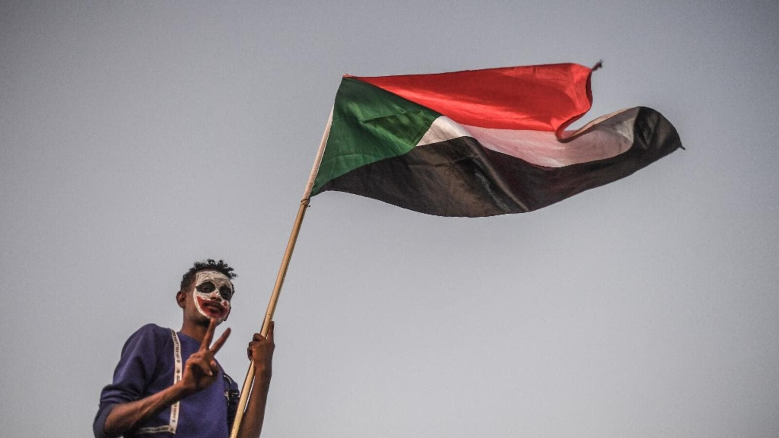 A Sudanese protestor waves a national flag during a protest  (AFP)