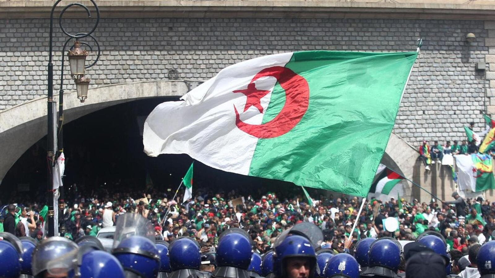 Algerian protesters wave a national flag as security forces stand guard during an an anti-government demonstration in Algiers on April 12, 2019. AFP