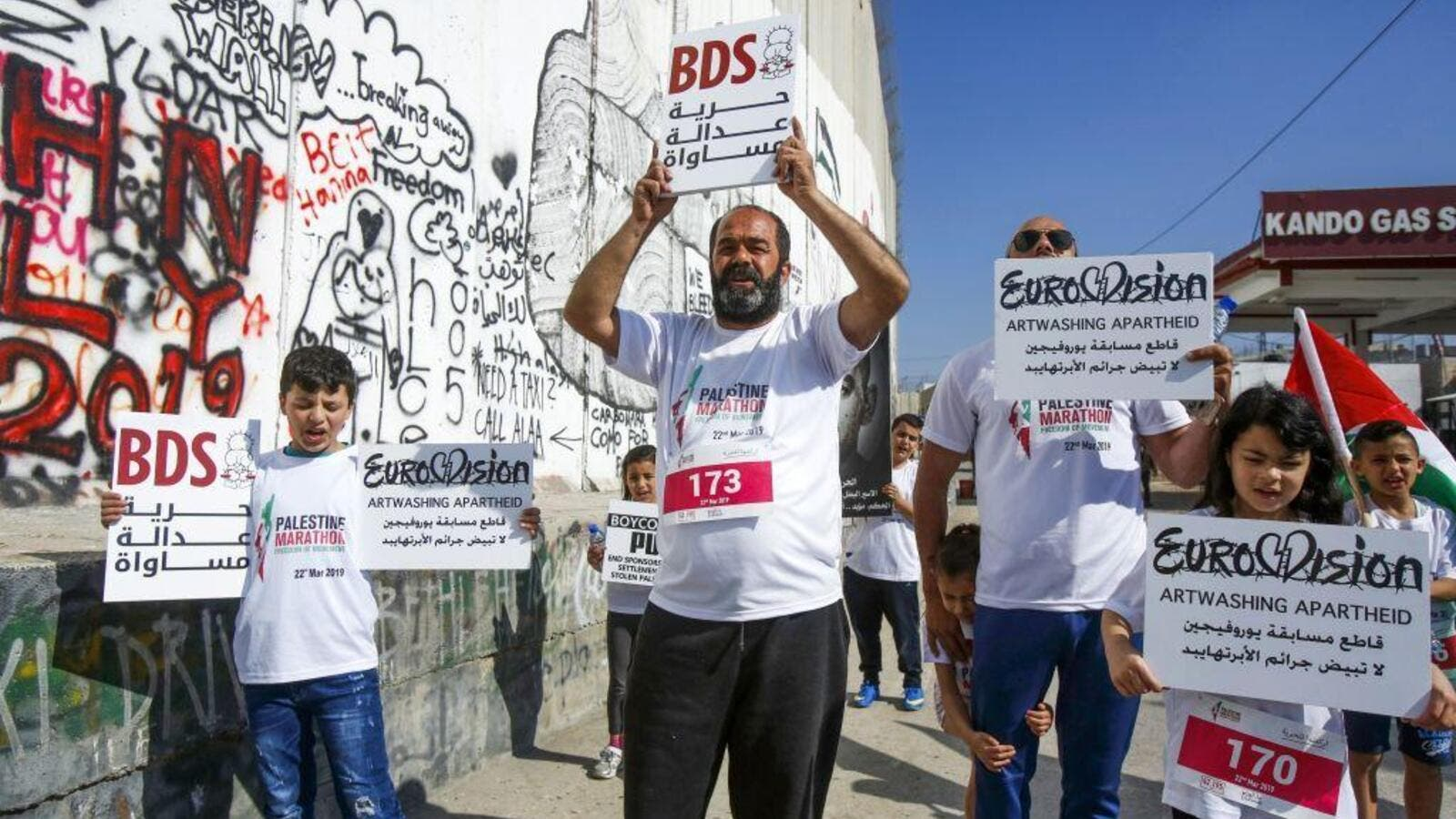 Activists hold banners calling for the boycott of Eurovision in the biblical town of Bethlehem in the occupied West Bank on 22 March 2019 [Musa AL ShaerAFP]
