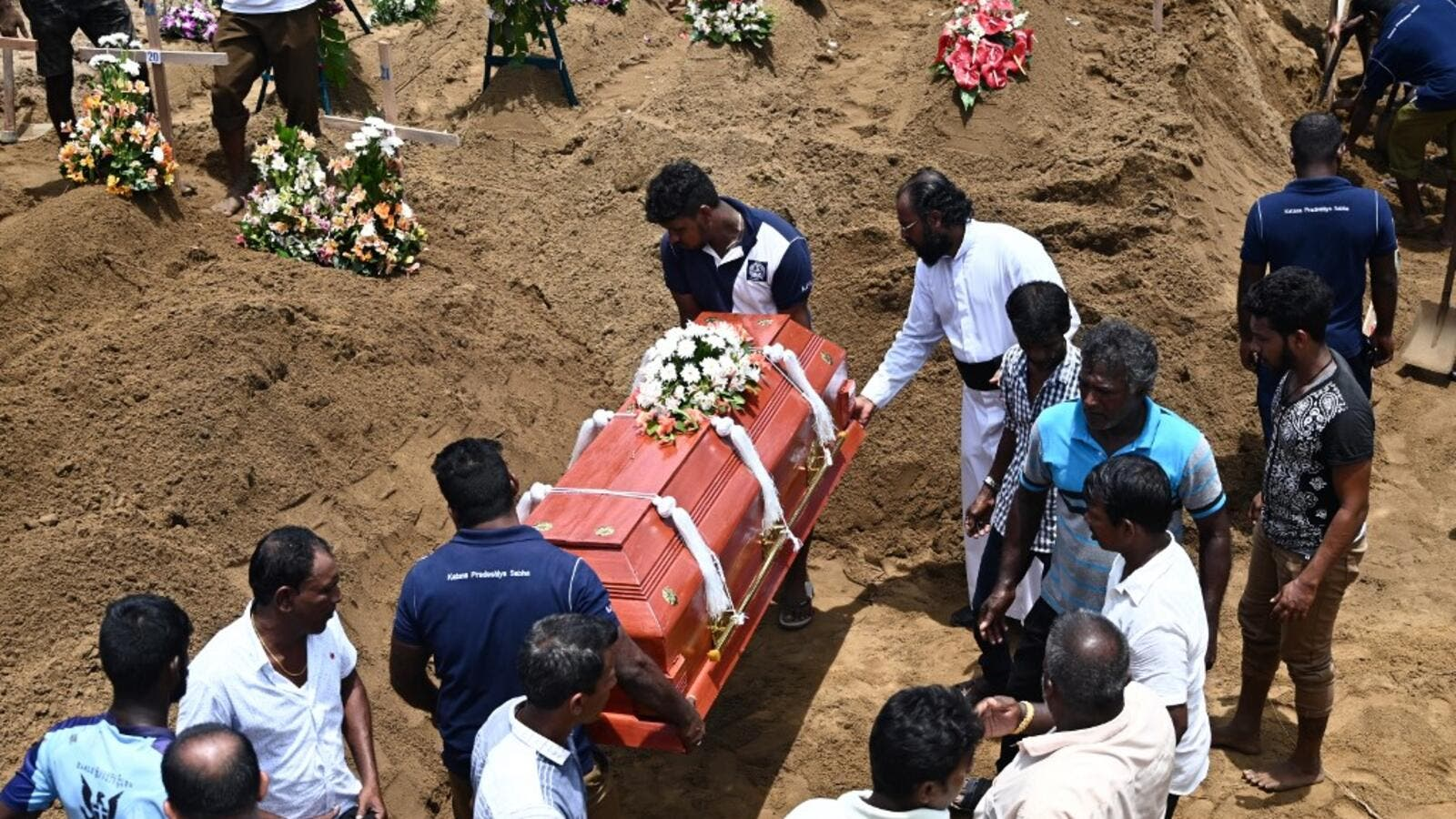 Relatives (R) watch as workers place the coffin of a bomb blast victim during a burial ceremony at a cemetery in Negombo on April 23, 2019. (AFP/ File)