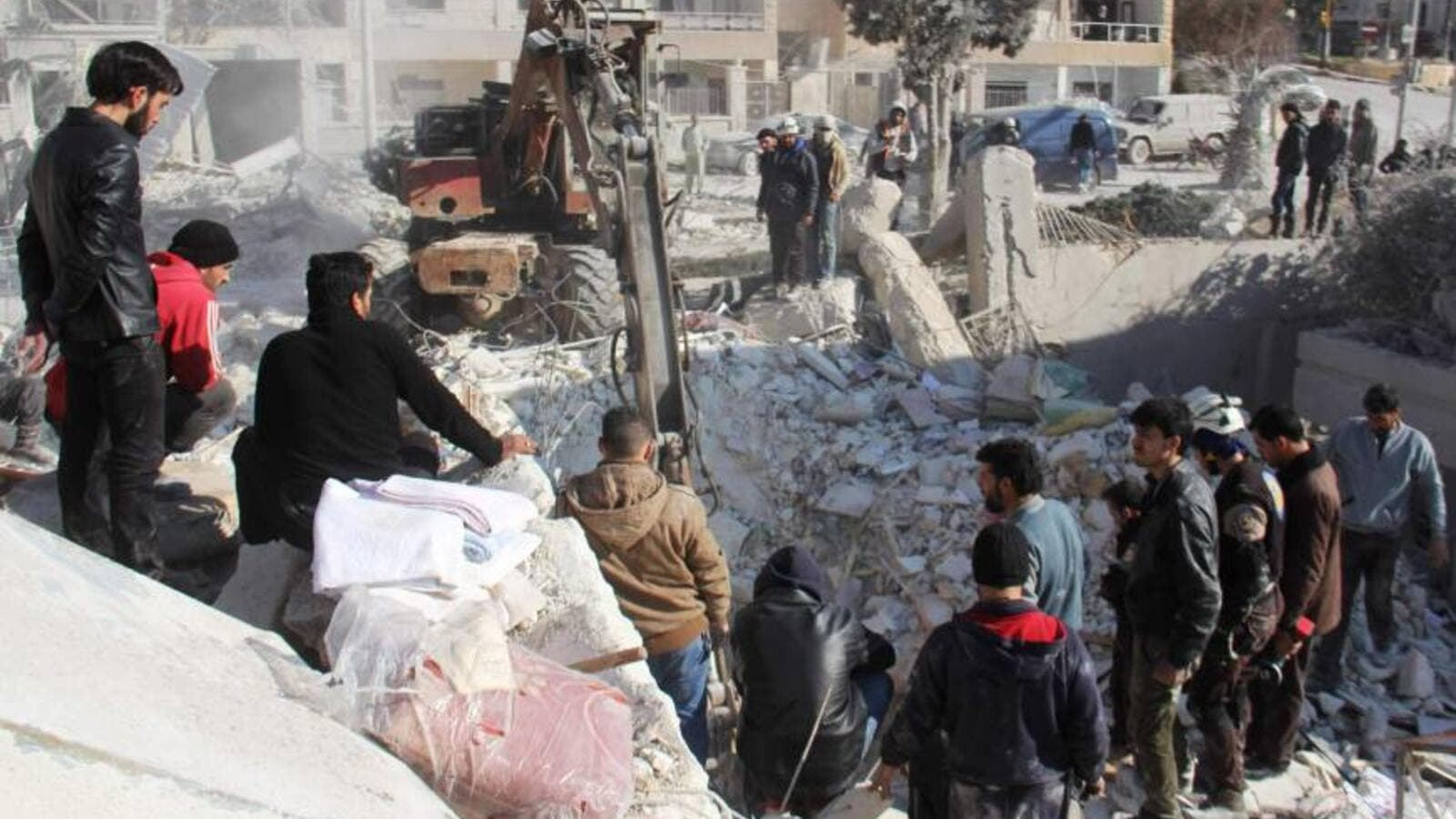 Syrian men and civil defense volunteers search for survivors amid the rubble of a building following airstrike on the northwestern city of Idlib. (AFP)
